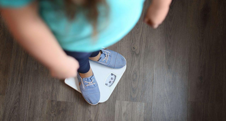 As consequências da obesidade em uma menina com excesso de peso em pé em uma balança